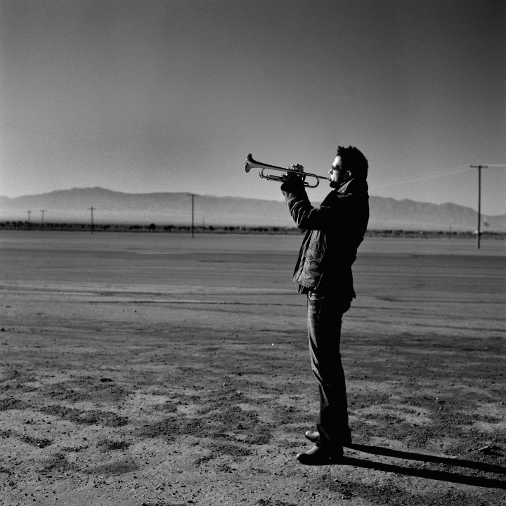 Till playing trumpet in desert, facing left