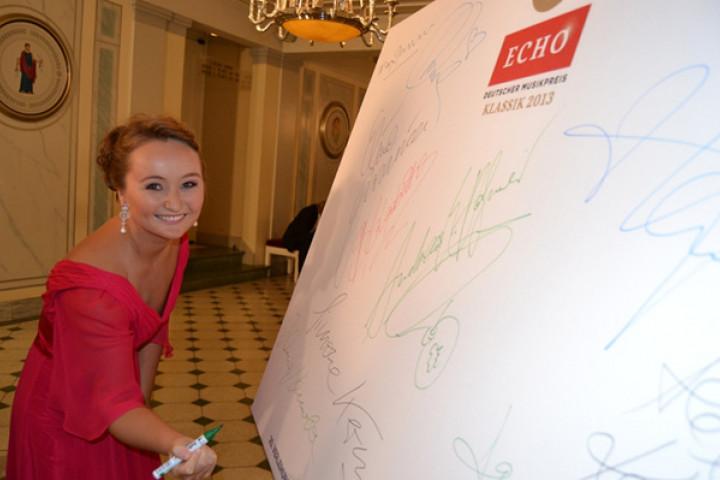 """Julia Lezhneva signiert die Leinwand für """"Ein Herz für Kinder"""""""